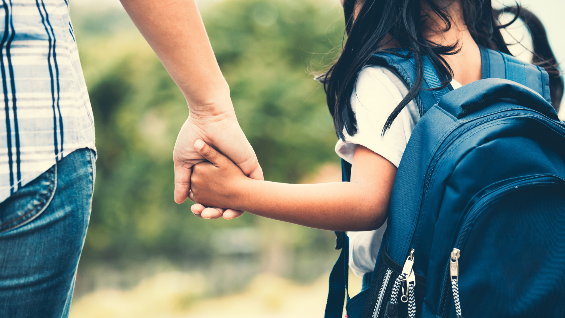 Student and parent holding hands
