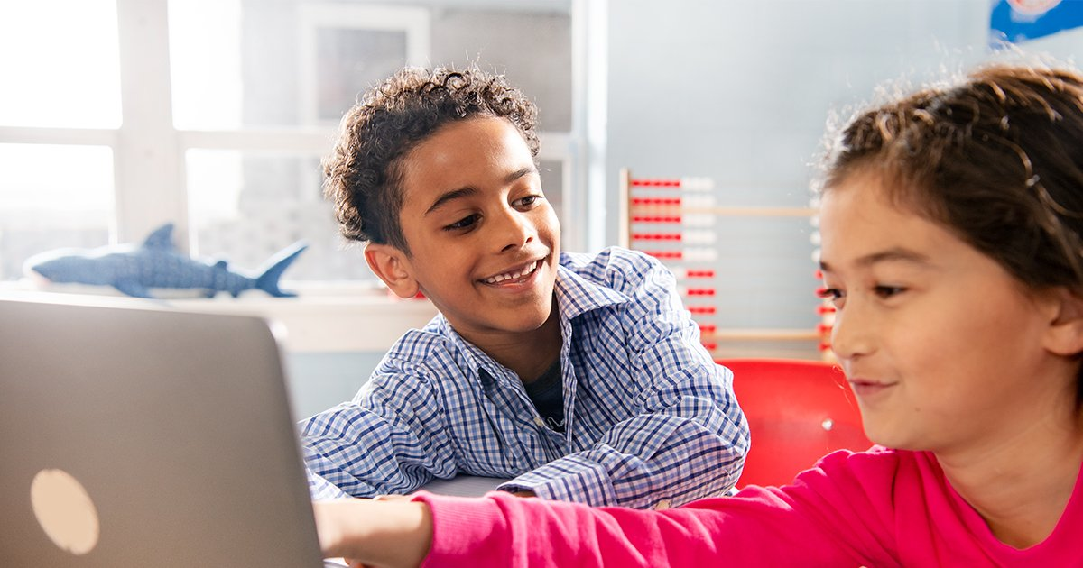 A boy and girl sitting at a desk looking at a shared computer screen.